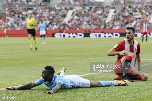 Manchester City's English midfielder Raheem Sterling falls down beside Girona's defender Pedro Alcala during the Costa Brava trophy friendly football...