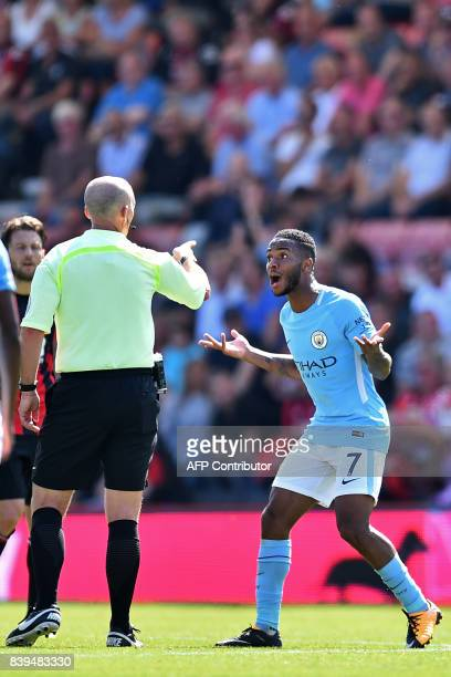 Manchester City's English midfielder Raheem Sterling gestures to English referee Mike Dean after he receives a second yellow card for going into the...