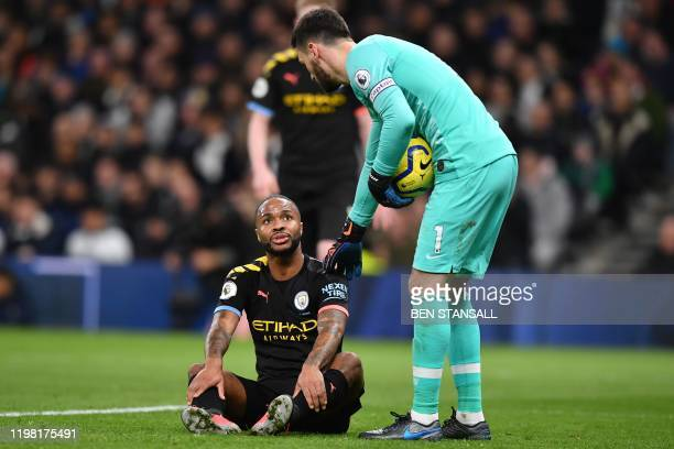 Manchester City's English midfielder Raheem Sterling goes down with an injury during the English Premier League football match between Tottenham...