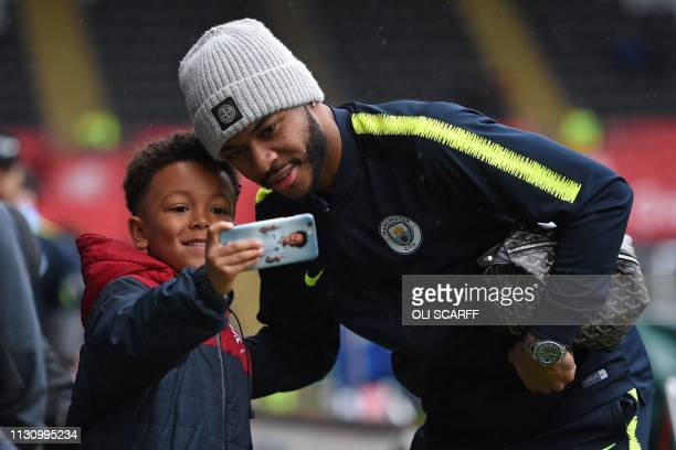 Manchester City's English midfielder Raheem Sterling has a selfie photograph taken with a young fan as he arrives for the FA Cup quarter-final...