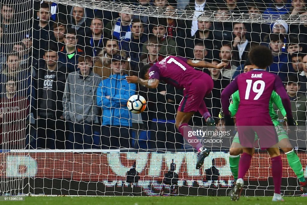 Manchester City's English midfielder Raheem Sterling (L) heads their second goal past Cardiff City's English-born Filipino goalkeeper Neil Etheridge during the English FA Cup fourth round football match between Cardiff City and Manchester City at Cardiff City Stadium in Cardiff, south Wales on January 28, 2018. / AFP PHOTO / Geoff CADDICK / RESTRICTED TO EDITORIAL USE. No use with unauthorized audio, video, data, fixture lists, club/league logos or 'live' services. Online in-match use limited to 75 images, no video emulation. No use in betting, games or single club/league/player publications. /
