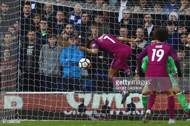 Manchester City's English midfielder Raheem Sterling heads their second goal past Cardiff City's English-born Filipino goalkeeper Neil Etheridge...