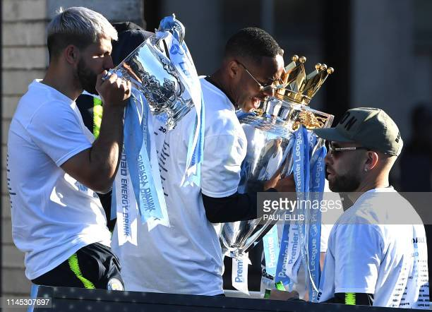 Manchester City's English midfielder Raheem Sterling holds the Premier League trophy as Manchester City's Argentinian striker Sergio Aguero drinks...