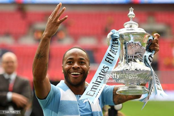 Manchester City's English midfielder Raheem Sterling holds the winner's trophy as the team celebrates victory after the English FA Cup final football...