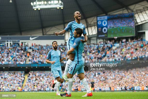 Manchester City's English midfielder Raheem Sterling is held aloft by teammate Manchester City's Spanish midfielder Nolito after scoring the opening...