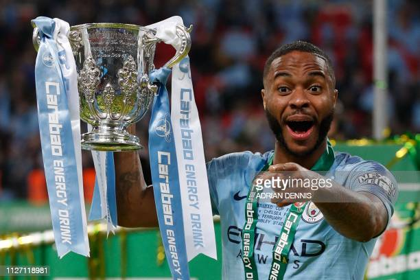 Manchester City's English midfielder Raheem Sterling lifts the trophy as Manchester City players celebrate their victory in the English League Cup...