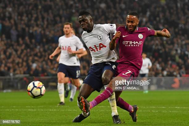Manchester City's English midfielder Raheem Sterling misses with this attempt under pressure from Tottenham Hotspur's Colombian defender Davinson...