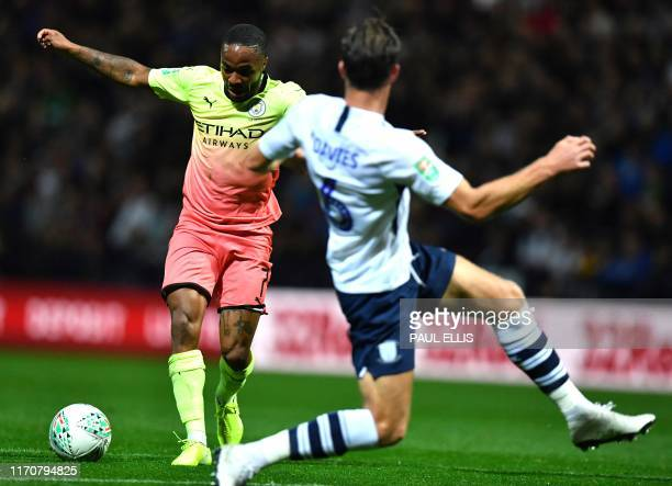 Manchester City's English midfielder Raheem Sterling runs on to scores his team's first goal during the English League Cup third round football match...