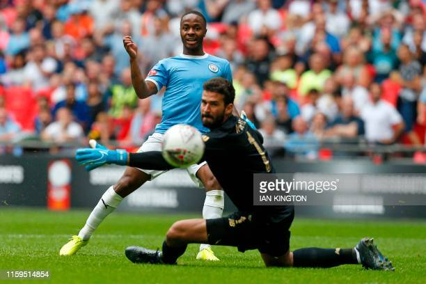 TOPSHOT Manchester City's English midfielder Raheem Sterling shoots past Liverpool's Brazilian goalkeeper Alisson Becker but hits the woodwork during...