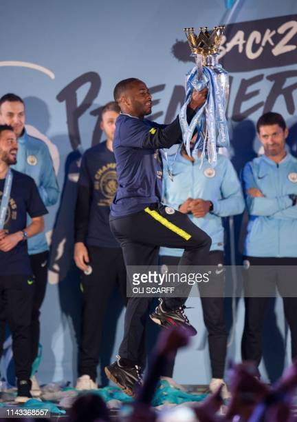 Manchester City's English midfielder Raheem Sterling shows the Premier League trophy to supporters outside the Etihad Stadium in Manchester northern...