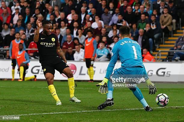 Manchester City's English midfielder Raheem Sterling slots the ball past Swansea City's Polish goalkeeper Lukasz Fabianski to score their third goal...