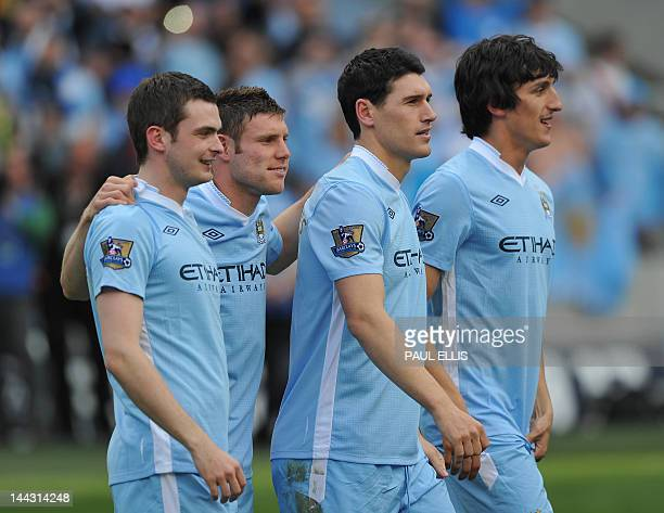 Manchester City's English midfielders Adam Johnson , James Milner , Gareth Barry and Montenegrin defender Stefan Savic celebrate on the pitch after...