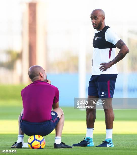 Manchester City's Fabian Delph talks with manager Pep Guardiola during the training session on March 16 2018 in Abu Dhabi United Arab Emirates
