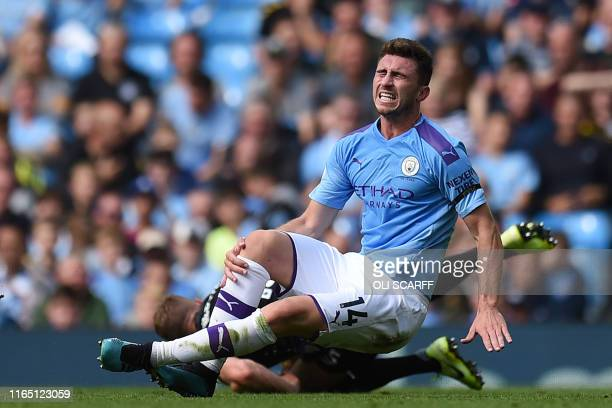 Manchester City's French defender Aymeric Laporte picks up an injury in a challenge with Brighton's English defender Adam Webster during the English...