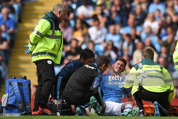 Manchester City's French defender Aymeric Laporte reacts after picking up an injury during the English Premier League football match between...