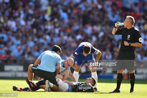 Manchester City's French defender Aymeric Laporte receives medical attention after picking up an injury during the English FA Community Shield...