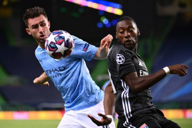 Manchester City's French defender Aymeric Laporte vies with Lyon's Cameroonian forward Karl Toko Ekambi during the UEFA Champions League quarterfinal...