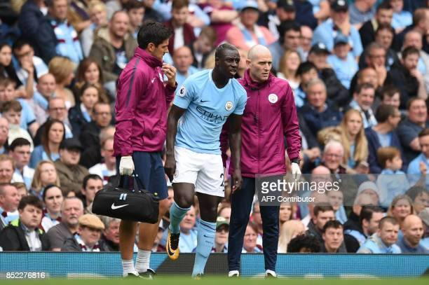 Manchester City's French defender Benjamin Mendy is helped by medics during the English Premier League football match between Manchester City and...