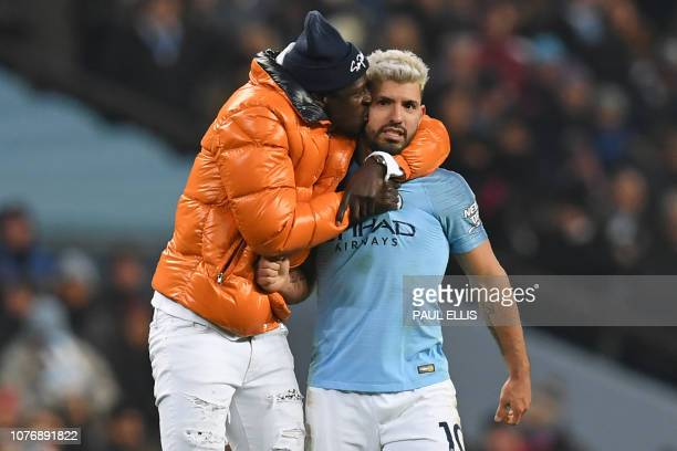Manchester City's French defender Benjamin Mendy plants a kiss on the cheek of Manchester City's Argentinian striker Sergio Aguero on the pitch after...