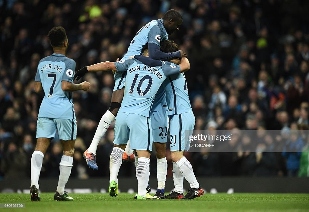 Manchester City's French defender Gael Clichy (unseen) is mobbed by teammates as he celebrates scoring his team's first goal during the English Premier League football match between Manchester City and Burnley at the Etihad Stadium in Manchester, north west England, on January 2, 2017. / AFP / Oli SCARFF / RESTRICTED TO EDITORIAL USE. No use with unauthorized audio, video, data, fixture lists, club/league logos or 'live' services. Online in-match use limited to 75 images, no video emulation. No use in betting, games or single club/league/player publications. /