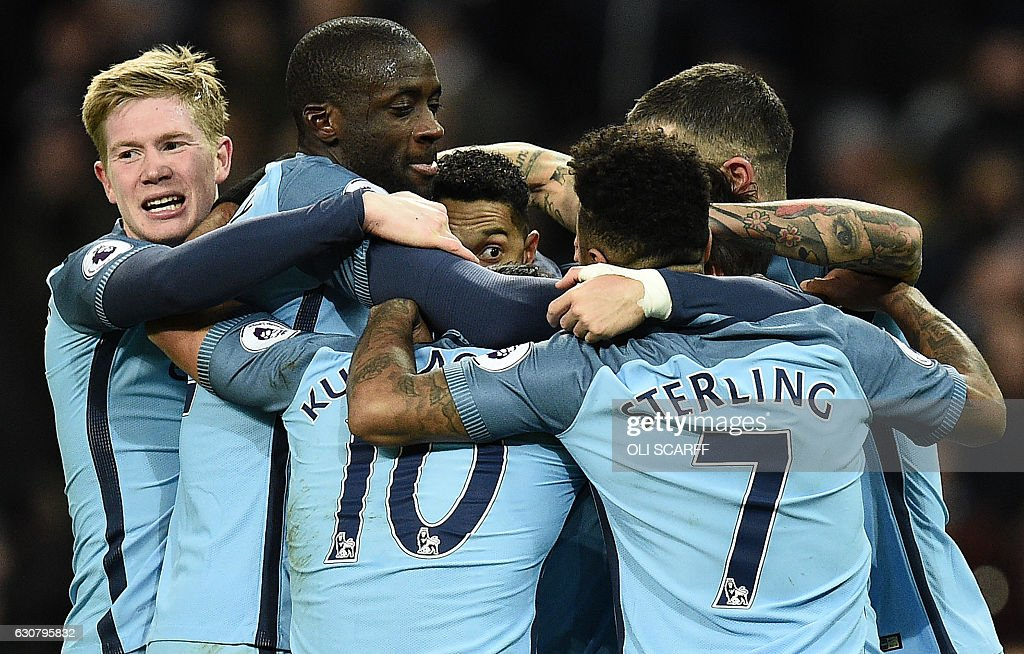 Manchester City's French defender Gael Clichy (C) is mobbed by teammates as he celebrates scoring his team's first goal during the English Premier League football match between Manchester City and Burnley at the Etihad Stadium in Manchester, north west England, on January 2, 2017. / AFP / Oli SCARFF / RESTRICTED TO EDITORIAL USE. No use with unauthorized audio, video, data, fixture lists, club/league logos or 'live' services. Online in-match use limited to 75 images, no video emulation. No use in betting, games or single club/league/player publications. /