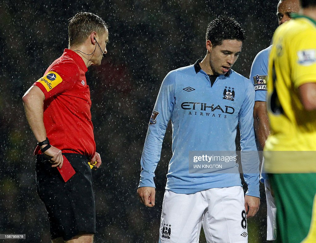"""Manchester City's French midfielder Samir Nasri (R) is sent off by referee Mike Jones after confronting Norwich City's Cameroonian defender Sebastien Bassong during the English Premier League football match between Norwich City and Manchester City at Carrow Road stadium in Norwich, England on December 29, 2012. USE. No use with unauthorized audio, video, data, fixture lists, club/league logos or """"live"""" services. Online in-match use limited to 45 images, no video emulation. No use in betting, games or single club/league/player publications."""