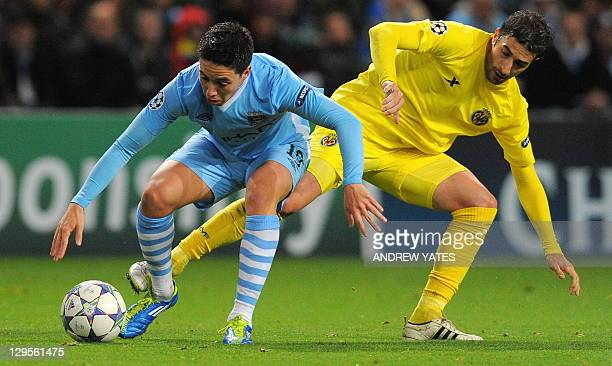 Manchester City's French midfielder Samir Nasri vies with Villarreal's Spanish midfielder Cani during their UEFA Champions league football match...