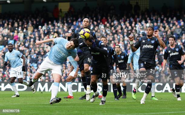 Manchester City's Gareth Barry stoops to win an header against Portsmouth's Angelos Basinas