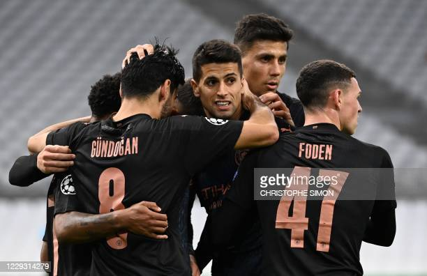 Manchester City's German midfielder Ilkay Gundogan celebrates with team mates after scoring a goal during the UEFA Champions League Group C football...
