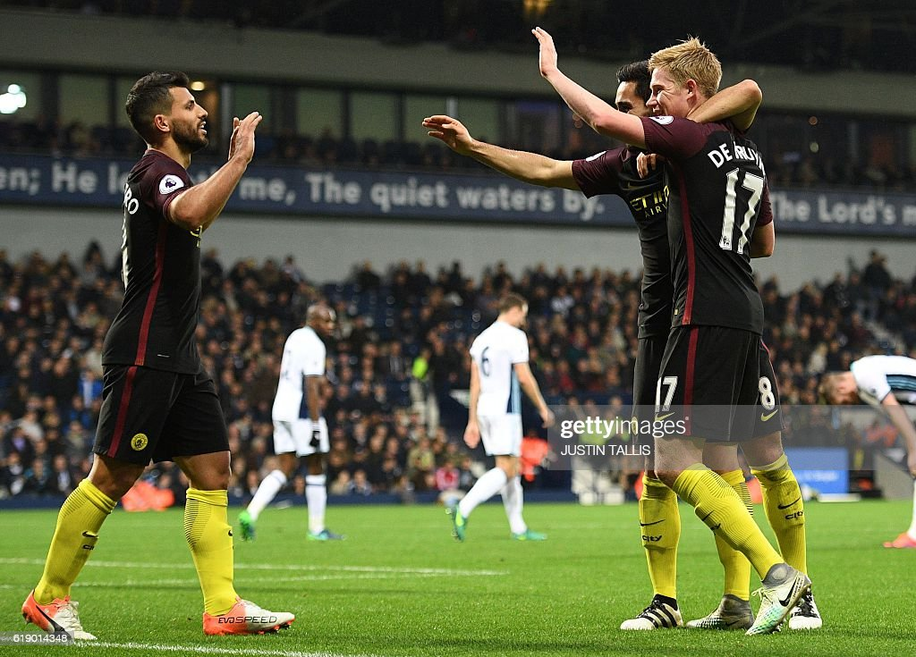 Manchester City's German midfielder Ilkay Gundogan (2nd R) celebrates with Manchester City's Belgian midfielder Kevin De Bruyne and Manchester City's Argentinian striker Sergio Aguero (L) after scoring their fourth goal during the English Premier League football match between West Bromwich Albion and Manchester City at The Hawthorns stadium in West Bromwich, central England, on October 29, 2016. Manchester City won the game 4-0. / AFP / Justin TALLIS / RESTRICTED TO EDITORIAL USE. No use with unauthorized audio, video, data, fixture lists, club/league logos or 'live' services. Online in-match use limited to 75 images, no video emulation. No use in betting, games or single club/league/player publications. /
