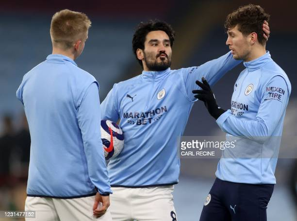 Manchester City's German midfielder Ilkay Gundogan jokes with Manchester City's English defender John Stones as they warms up ahead of during the...