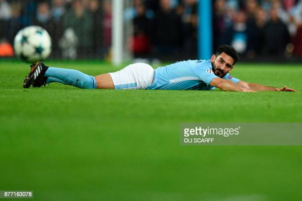 Manchester City's German midfielder Ilkay Gundogan looks on from the pitch after he went down in a challenge with nothing given during the UEFA...