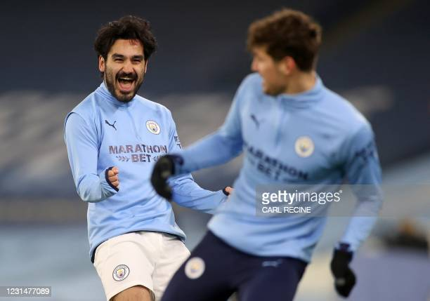 Manchester City's German midfielder Ilkay Gundogan shares a joke with Manchester City's English defender John Stones as they warms up ahead of during...