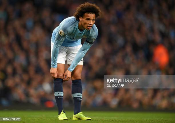 Manchester City's German midfielder Leroy Sane adjusts his socks during the English Premier League football match between Manchester City and...