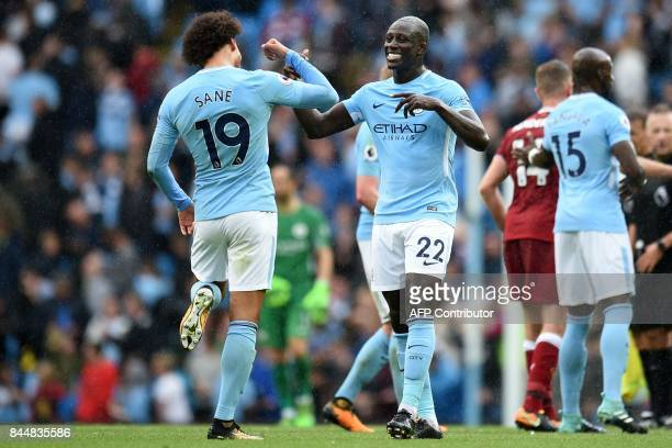 Manchester City's German midfielder Leroy Sane and Manchester City's French defender Benjamin Mendy celebrate at the final whistle in the English...