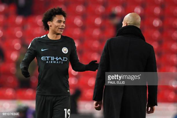 Manchester City's German midfielder Leroy Sane chats with Manchester City's Spanish manager Pep Guardiola on the pitch after the English Premier...