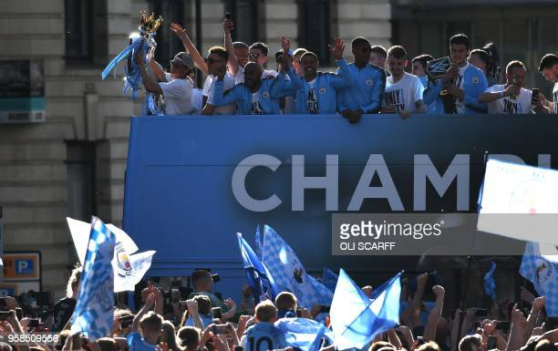 Manchester City's German midfielder Leroy Sane holds up the Premier League trophy to fans as the Manchester City team take part in an opentop bus...