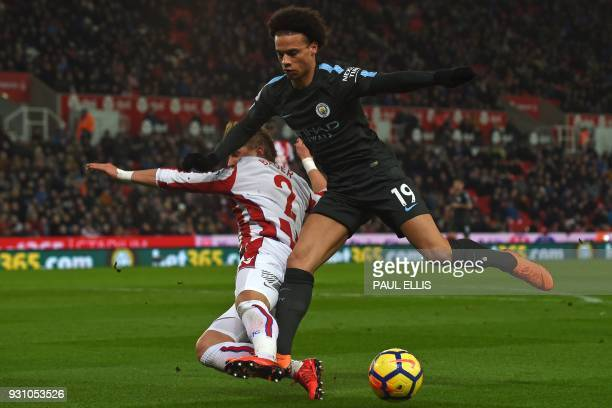 Manchester City's German midfielder Leroy Sane is tackled by Stoke City's Austrian defender Moritz Bauer during the English Premier League football...