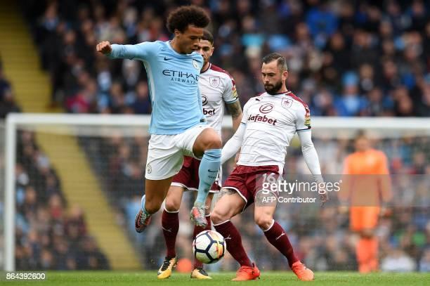 Manchester City's German midfielder Leroy Sane jumps a challenge from Burnley's Belgian midfielder Steven Defour during the English Premier League...