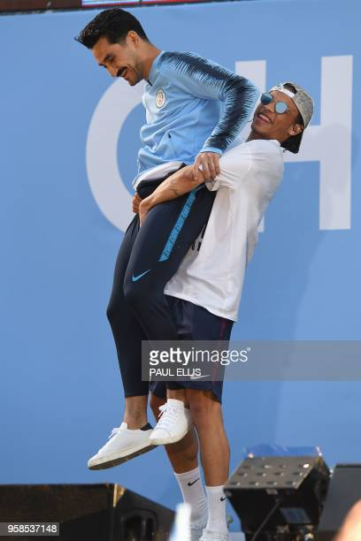 Manchester City's German midfielder Leroy Sane lifts Manchester City's German midfielder Ilkay Gundogan as htey attend an event for fans with members...