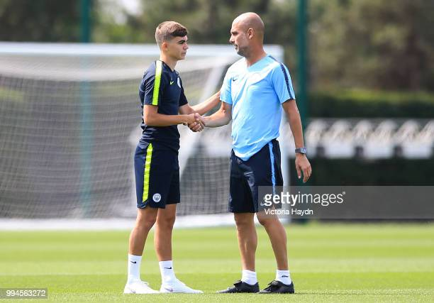 Manchester City's Iker Pozo greets manager Pep Guardiola during training at Manchester City Football Academy on July 6 2018 in Manchester England