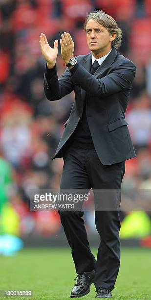 Manchester City's Italian manager Roberto Mancini applauds the fans after the English Premier League football match between Manchester United and...