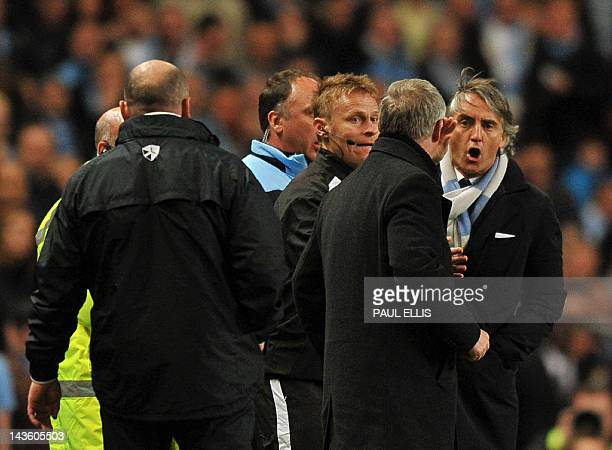 Manchester City's Italian manager Roberto Mancini exchanges words with Manchester United manager Alex Ferguson during their English Premier League...