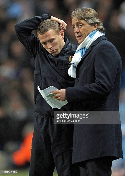 Manchester City's Italian manager Roberto Mancini talks to Manchester City's Welsh forward Craig Bellamy during the English Premier League football...