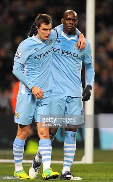 Manchester City's Italian striker Mario Balotelli celebrates with English midfielder Adam Johnson after scoring their fourth goal of the English...