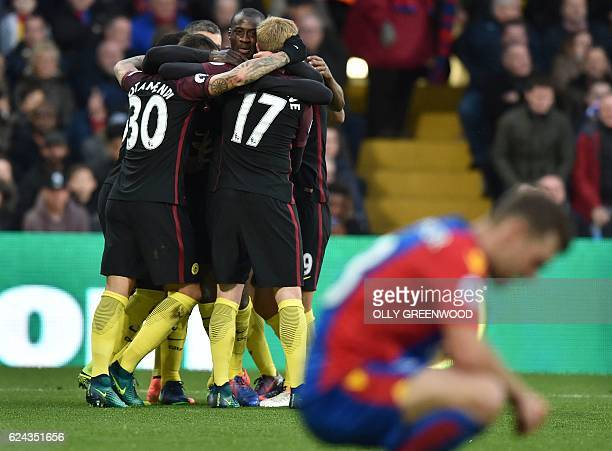 Manchester City's Ivorian midfielder Yaya Toure celebrates with teammates after scoring the opening goal during the English Premier League football...