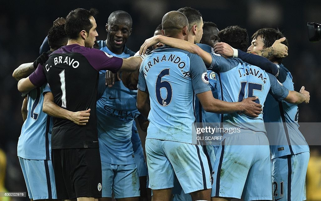 Manchester City's Ivorian midfielder Yaya Toure celebrates with teammates following the English Premier League football match between Manchester City and Arsenal at the Etihad Stadium in Manchester, north west England, on December 18, 2016. Manchester City won the match 2-1. / AFP / Oli SCARFF / RESTRICTED TO EDITORIAL USE. No use with unauthorized audio, video, data, fixture lists, club/league logos or 'live' services. Online in-match use limited to 75 images, no video emulation. No use in betting, games or single club/league/player publications. /