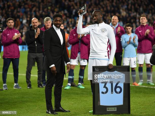 Manchester City's Ivorian midfielder Yaya Toure holds up an award by his brother Kolo after playing for the last time for City in the English Premier...