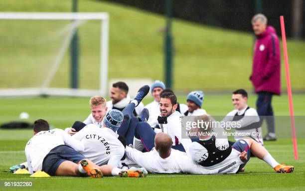 Manchester City's Kevin de Bruyne and Bernardo Silva share a joke with teammates during training at Manchester City Football Academy on April 27 2018...