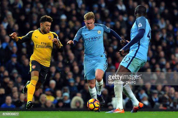 Manchester City's Kevin De Bruyne and Yaya Toure and Arsenal's Alex OxladeChamberlain in action during the Barclay's Premiership match at the Etihad...